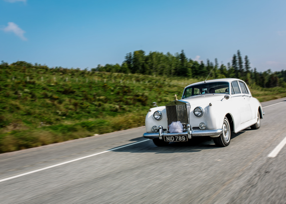 bride rides in vinatge rolls royce on their way to ale belvedere wedding in wakefield quebec