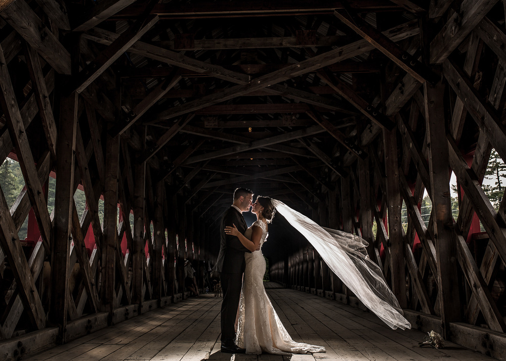 bride and groom take a portrait under the covered bridge in wakefield quebec