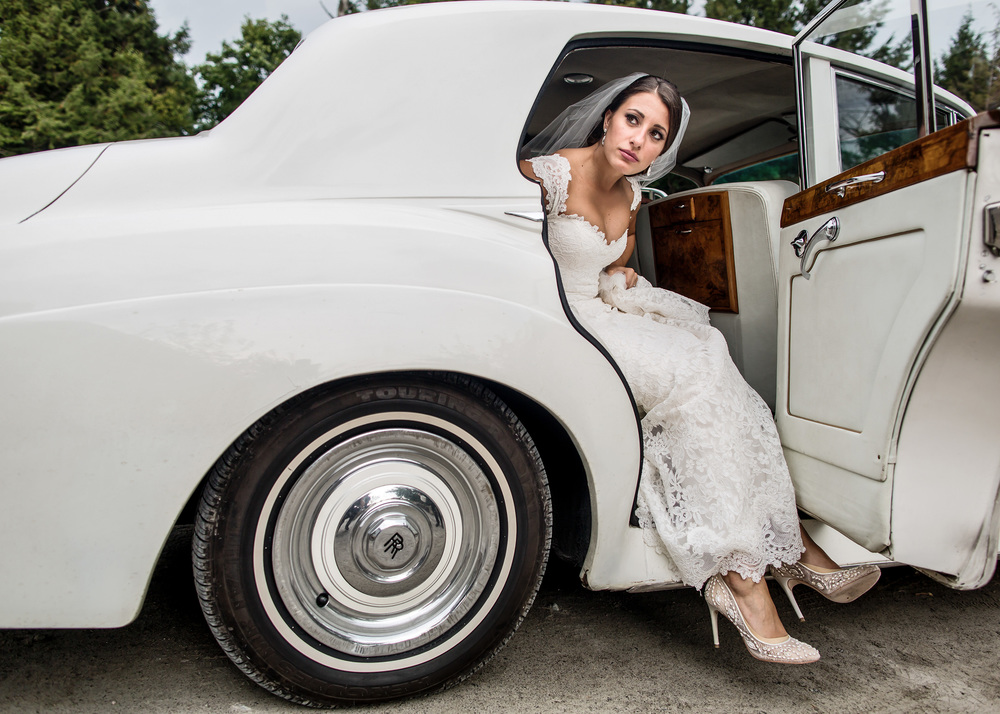 bride steps out of vintage rolls royce before wedding ceremony at le belvedere wedding in wakefield quebec