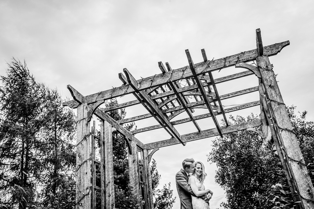 bride and groom pose underneath the gazebo at a strathmere wedding