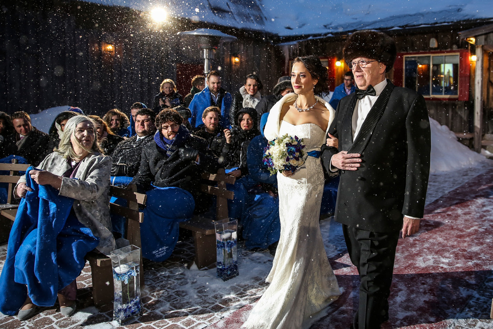 bride and father walk down aisle during a winter wedding ceremony at strathmere