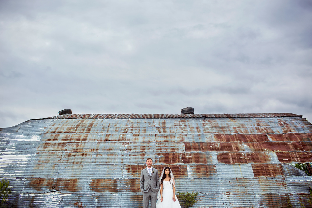 bride and groom pose outside an abandon garage in wakefield quebec