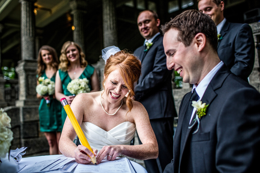 bride signs wedding license with big pencil during a ceremony at the rockcliffe park pavilion ottawa