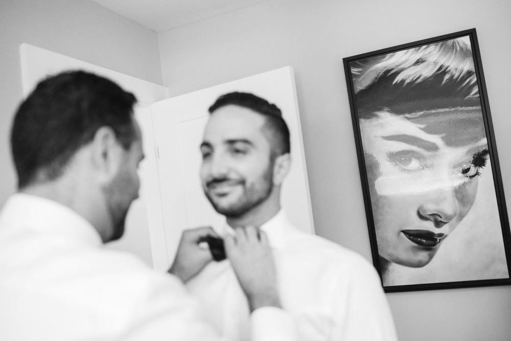 groom getting help to tie bowtie with artwork in the background