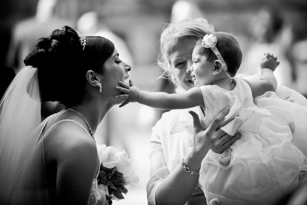 baby touching bride on wedding day