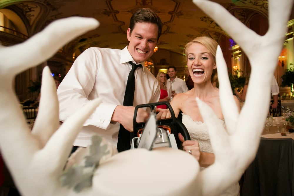 bride and groom cutting their cake with a chainsaw