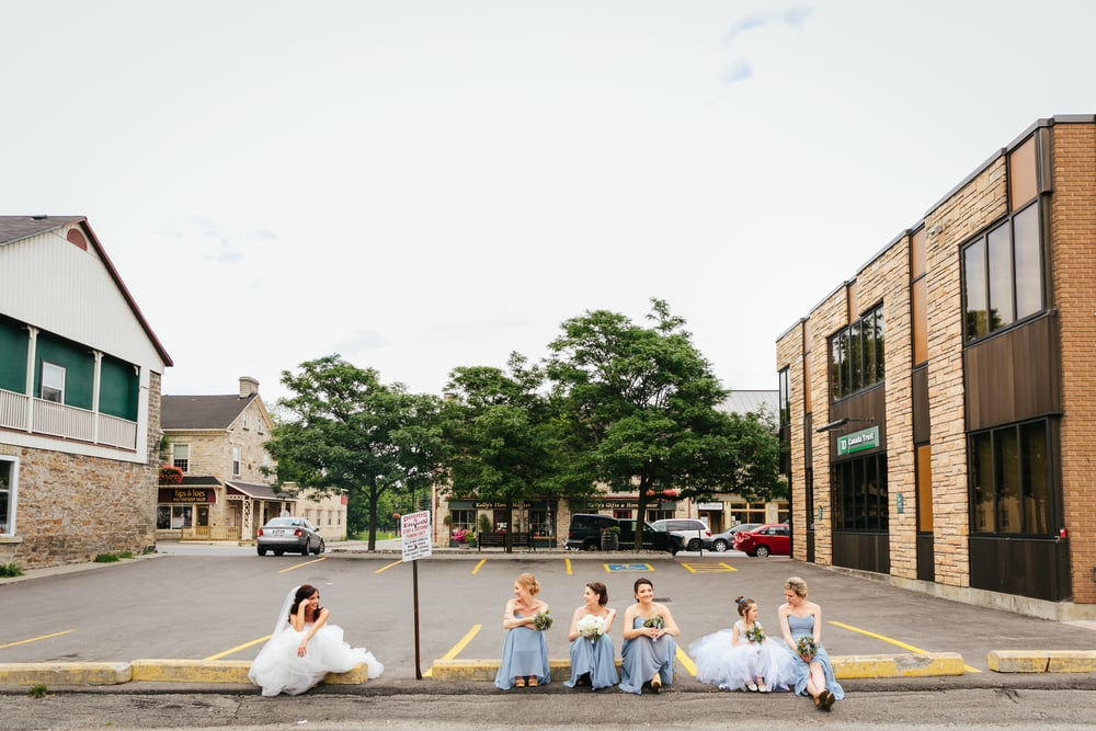 bridesmaids and brides sitting on a curb in perth