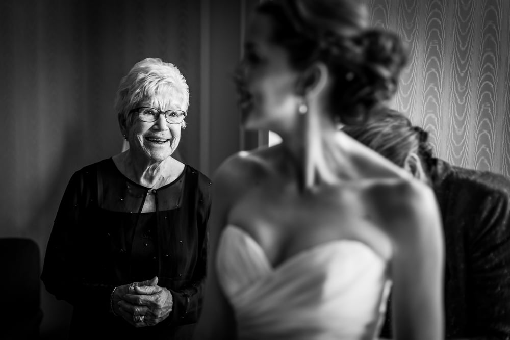 grandmother watching her grandaughter get into her wedding dress