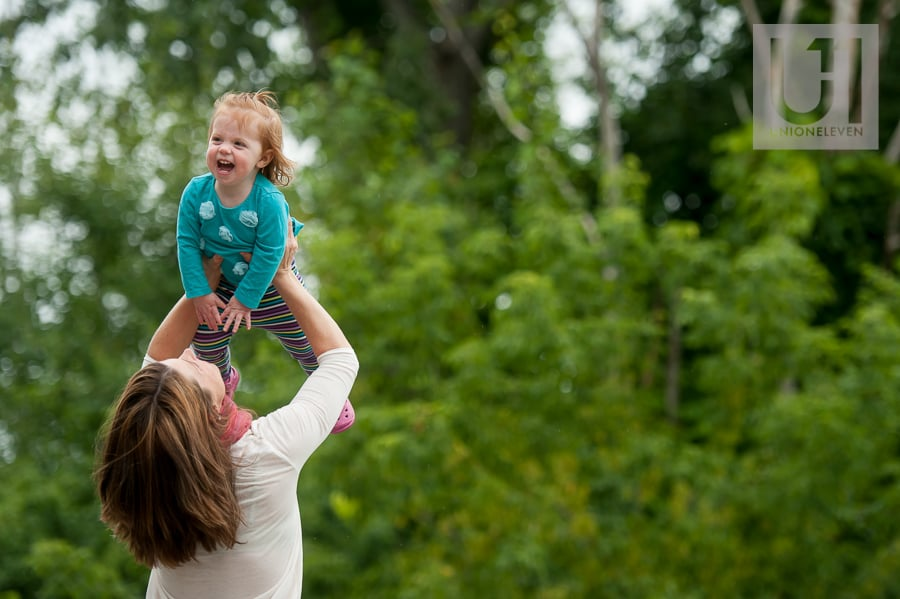 mom throwing her daughter in the air