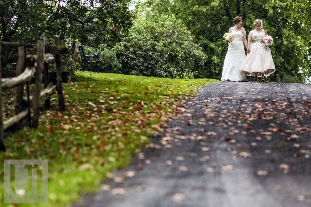 two brides walking down a path hand in hand