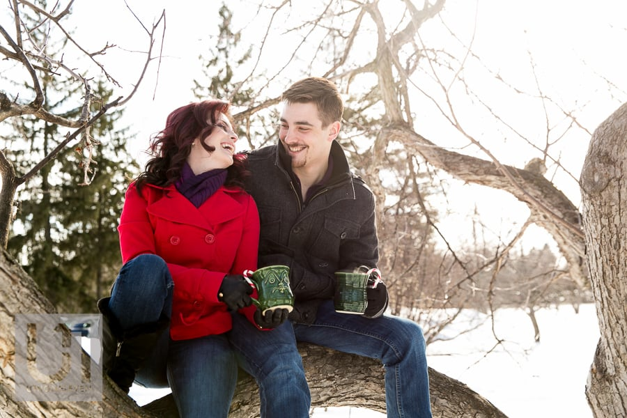 couple enjoying a mug of hot chocolate at a winter engagement shoot
