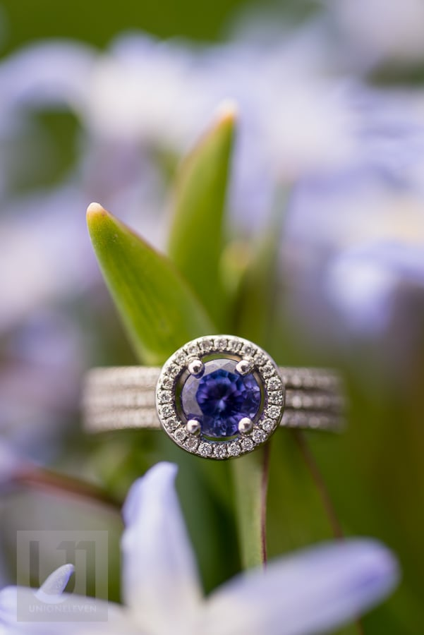 engagement ring with blue stone and diamonds resting on flower