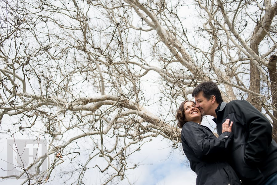 man kissing woman's cheek against tree and blue sky