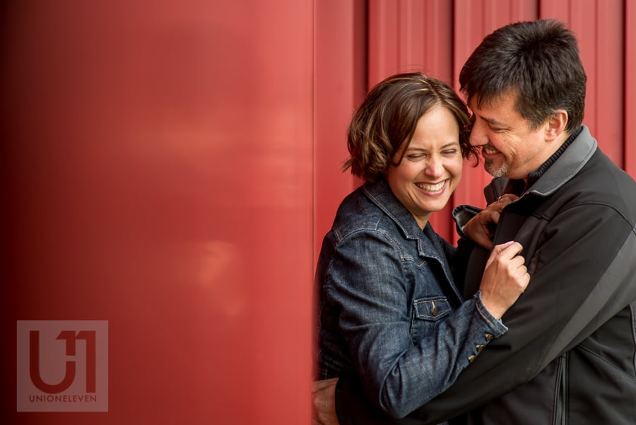 man and woman holding each other against red wall, laughing