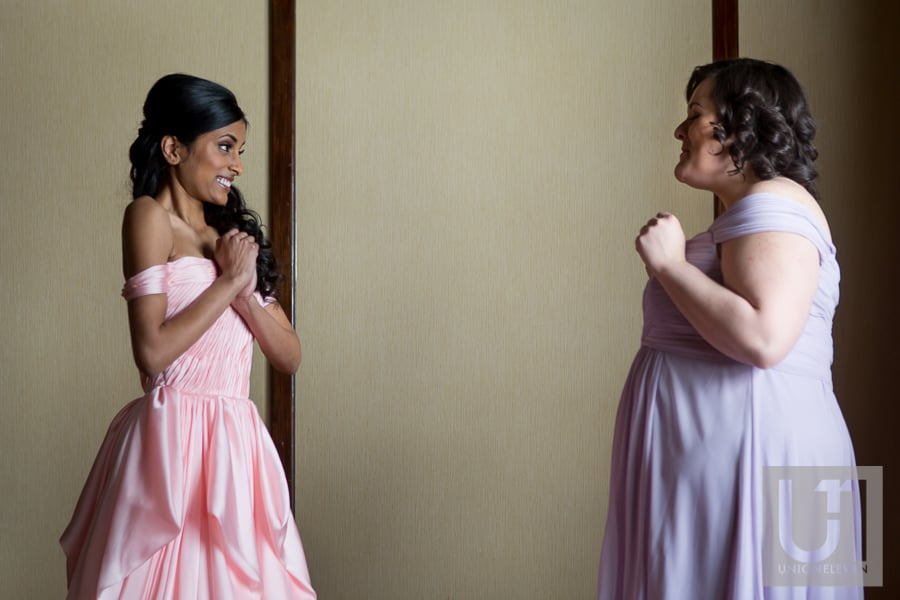 bride and bridesmaid giggling while getting ready