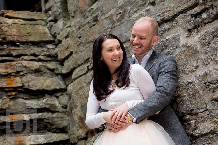 couple in an embrace against stone wall