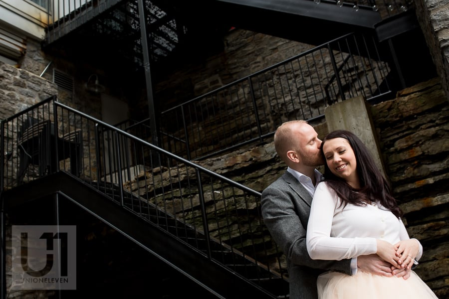 couple embracing chest to back by a stairwell at mill st. brew pub