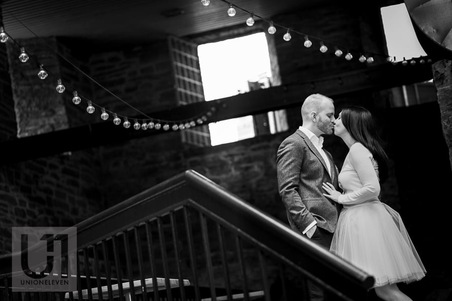 couple kissing in stairwell with overhanging light bulbs