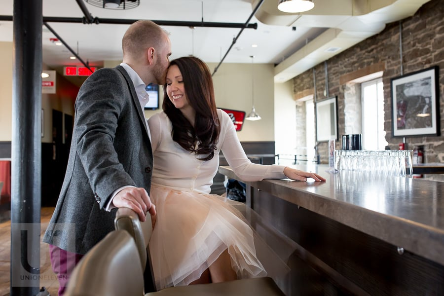 woman sitting on bar stool at mill st pub while man kisses her temple