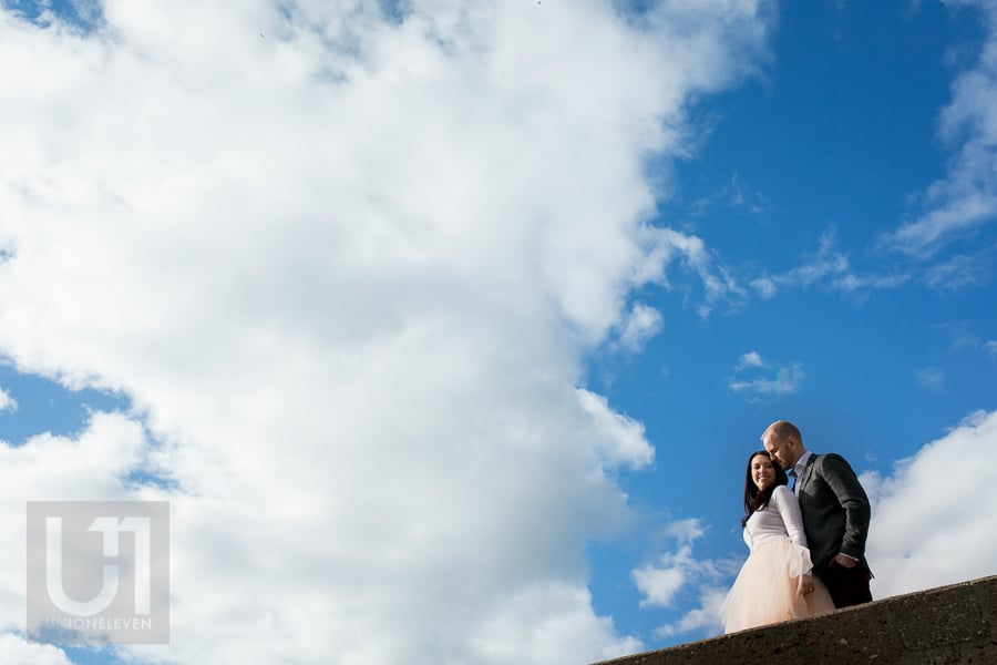 man and woman embracing against a bright blue sky full of white clouds