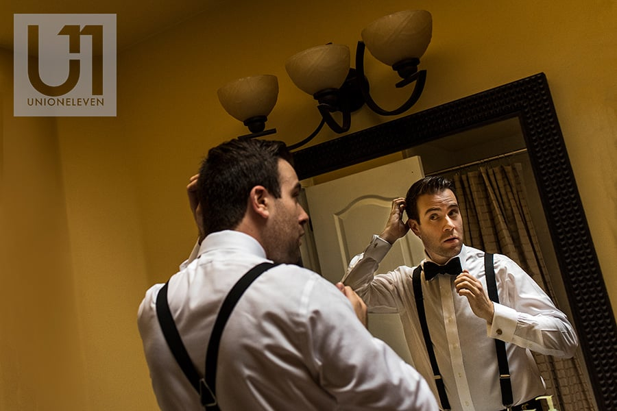 groom fixing hair in mirror ottawa wedding