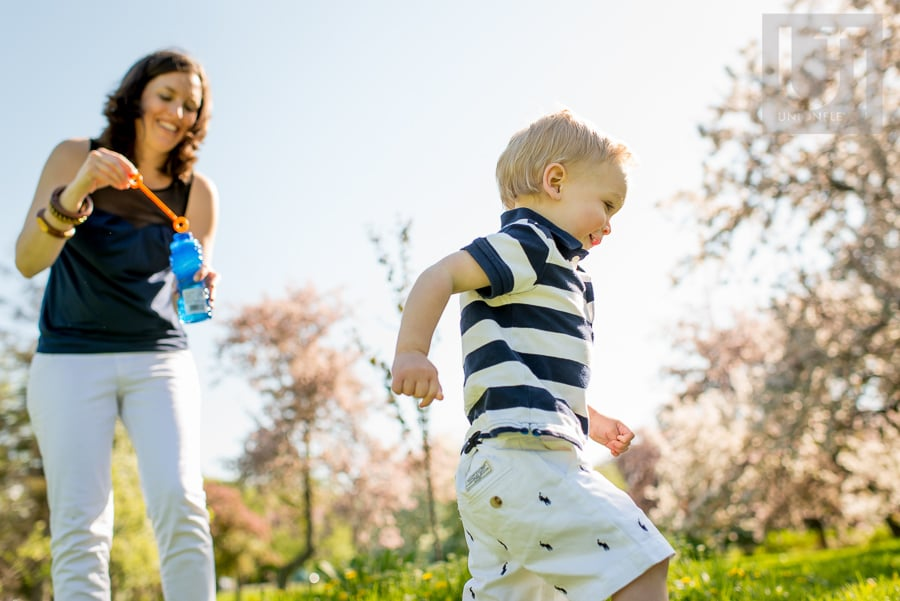 mother blowing bubbles while toddler runs around in field at Arboretum in Ottawa