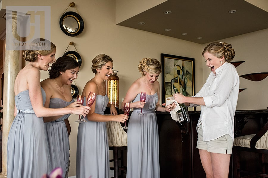 bride with bridesmaids spilling champaign during pre-ceremony of a le belvedere wedding in wakefield