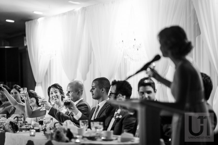 bride and groom at head table toasting their guests at wedding in Cornwall