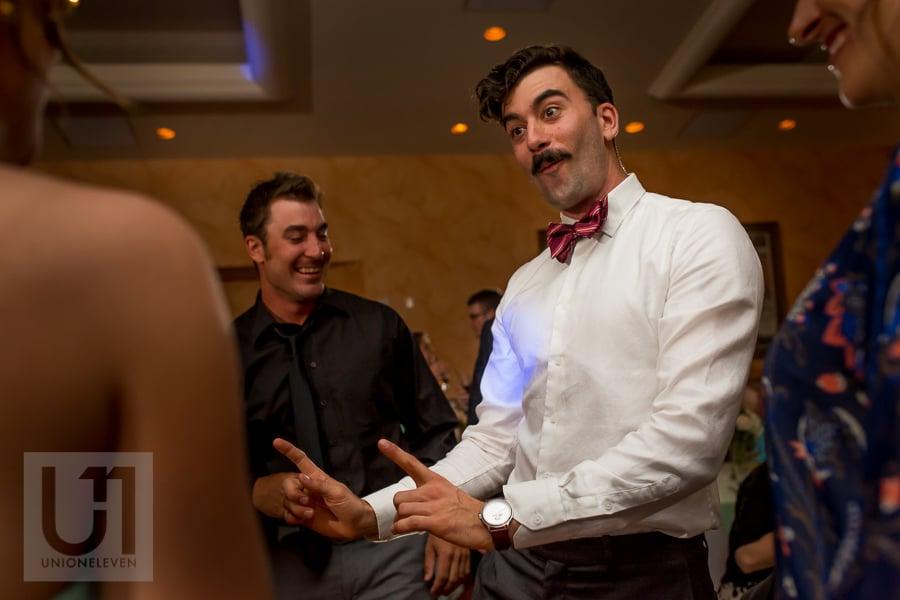 man with dark moustache and bowtie dancing on dance floor at wedding in Cornwall