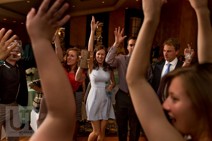 wedding guests dancing with their hands up in the air