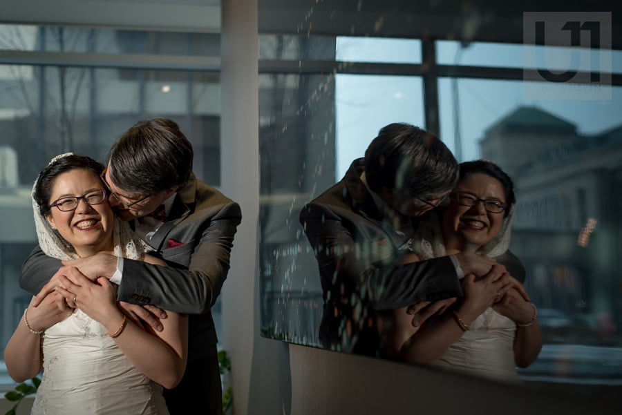 Bride and groom nuzzled in an embrace and laughing at Delta Hotel