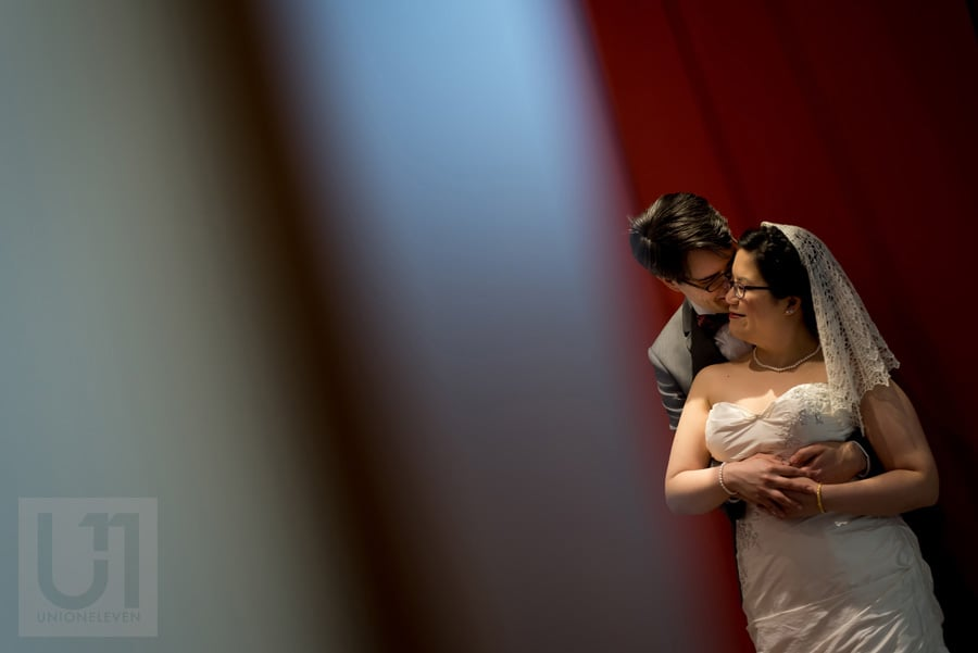 Groom hugging bride from behind in front of a red wall in Ottawa