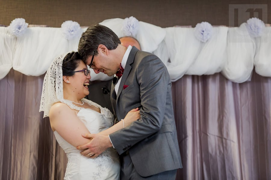 Bride and groom smiling in an embrace during wedding ceremony in Ottawa