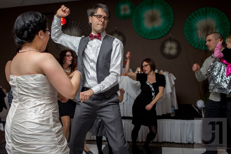 groom dancing with bride on dance floor with hand up in the air at ottawa wedding