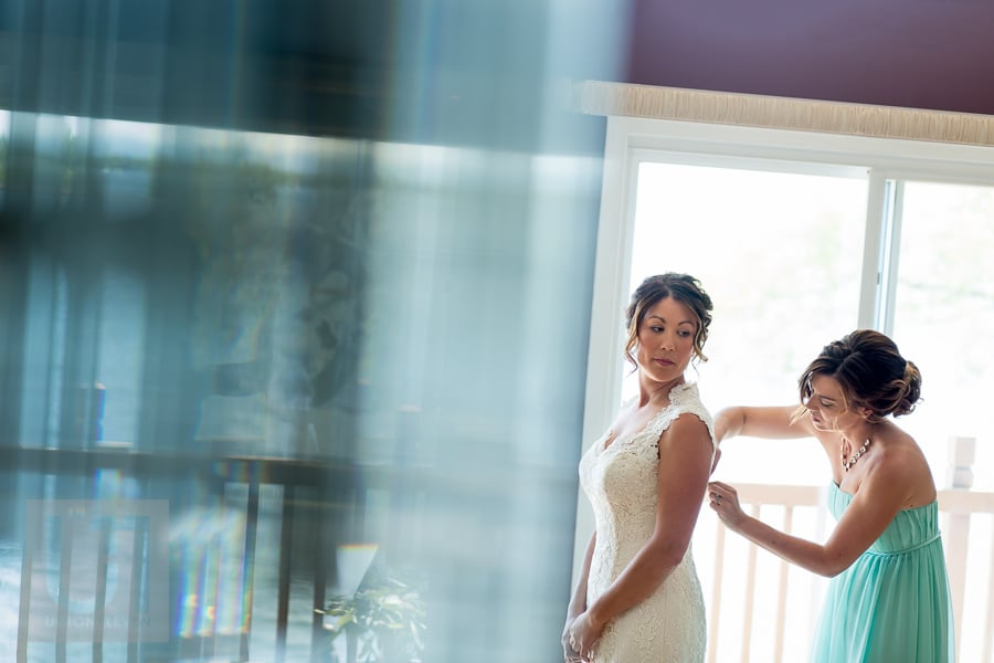 bride having her dress zipped by bridesmaid in front of large window