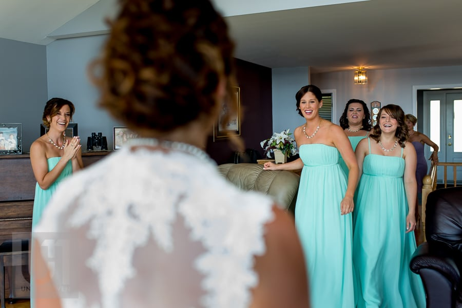 bride standing in front of her bridesmaids while they gaze at her, smiling