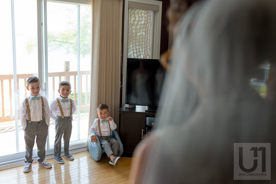 three young boys looking at bride, one pointing his finger and laughing at her
