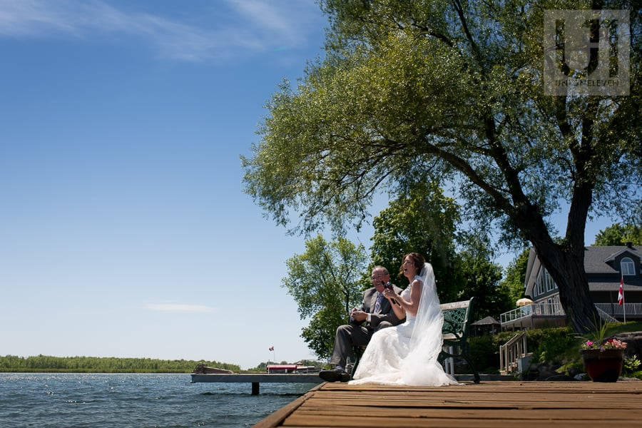 bride sitting in gown and veil, fishing on a dock with her a father in Cornwall, ON