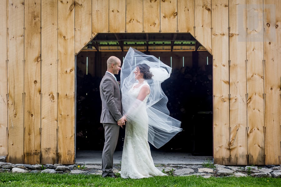 bride facing groom in front of barn, holding hands, veil blowing in her face