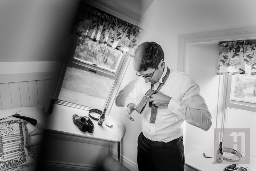 groom putting on a tie