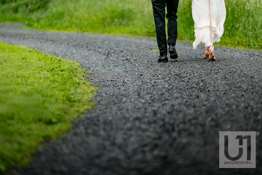 bride and groom walking down a path