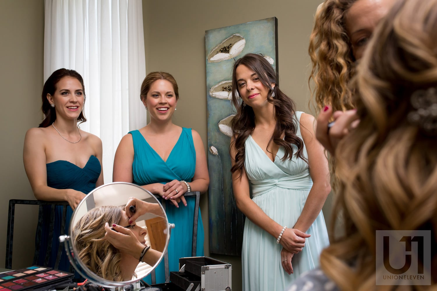 bride having makeup done while bridesmaids watch
