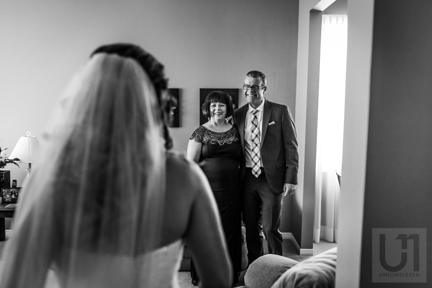 bride revealing herself in gown and veil to her parents on wedding day in Ottawa