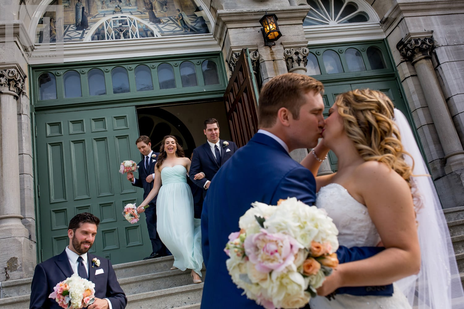 bride and groom kissing outside church while bridesmaids and groomsmen walk out