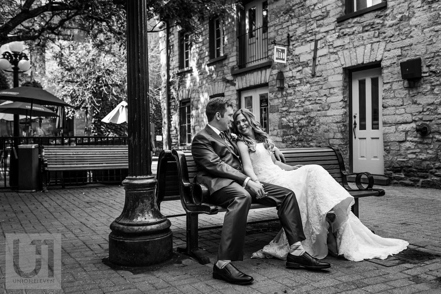 bride and groom sitting on bench in courtyard in Ottawa