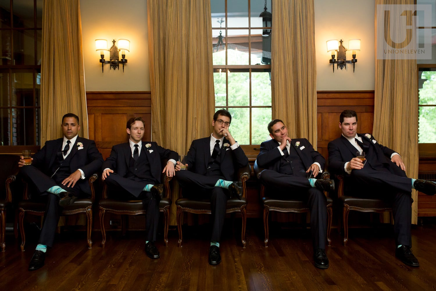 groomsmen sitting on chairs pensively at the Royal Ottawa Golf Club during wedding reception