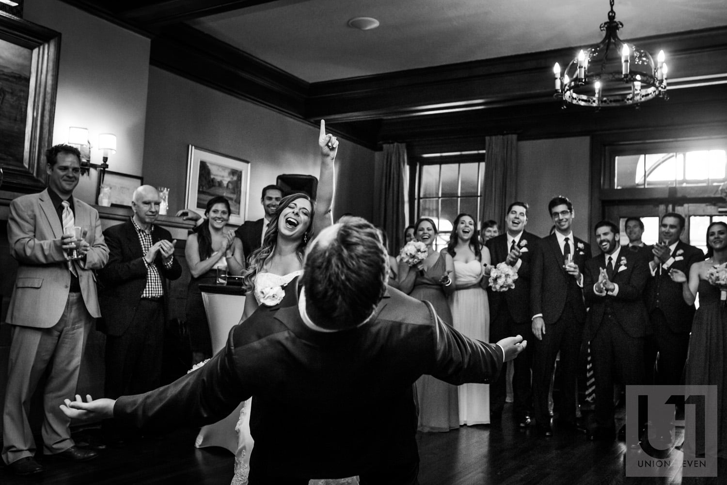 bride dancing with her finger in the air while groom leans backwards on dance floor at wedding reception in Gatineau