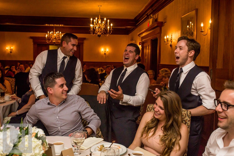 groomsmen singing and playing air guitar at table at wedding reception