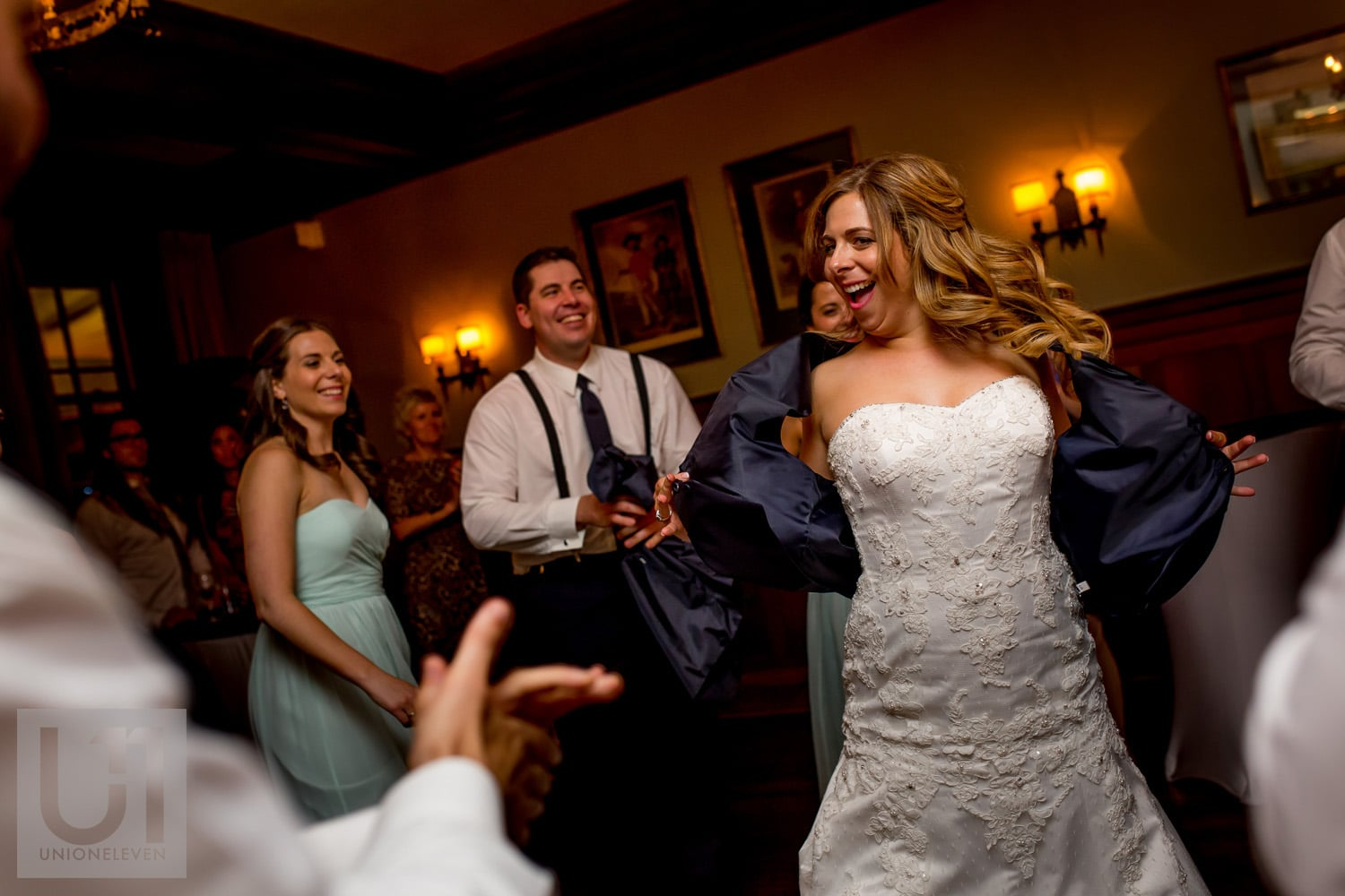 bride dancing with groomsman's vest surrounded by wedding party at reception