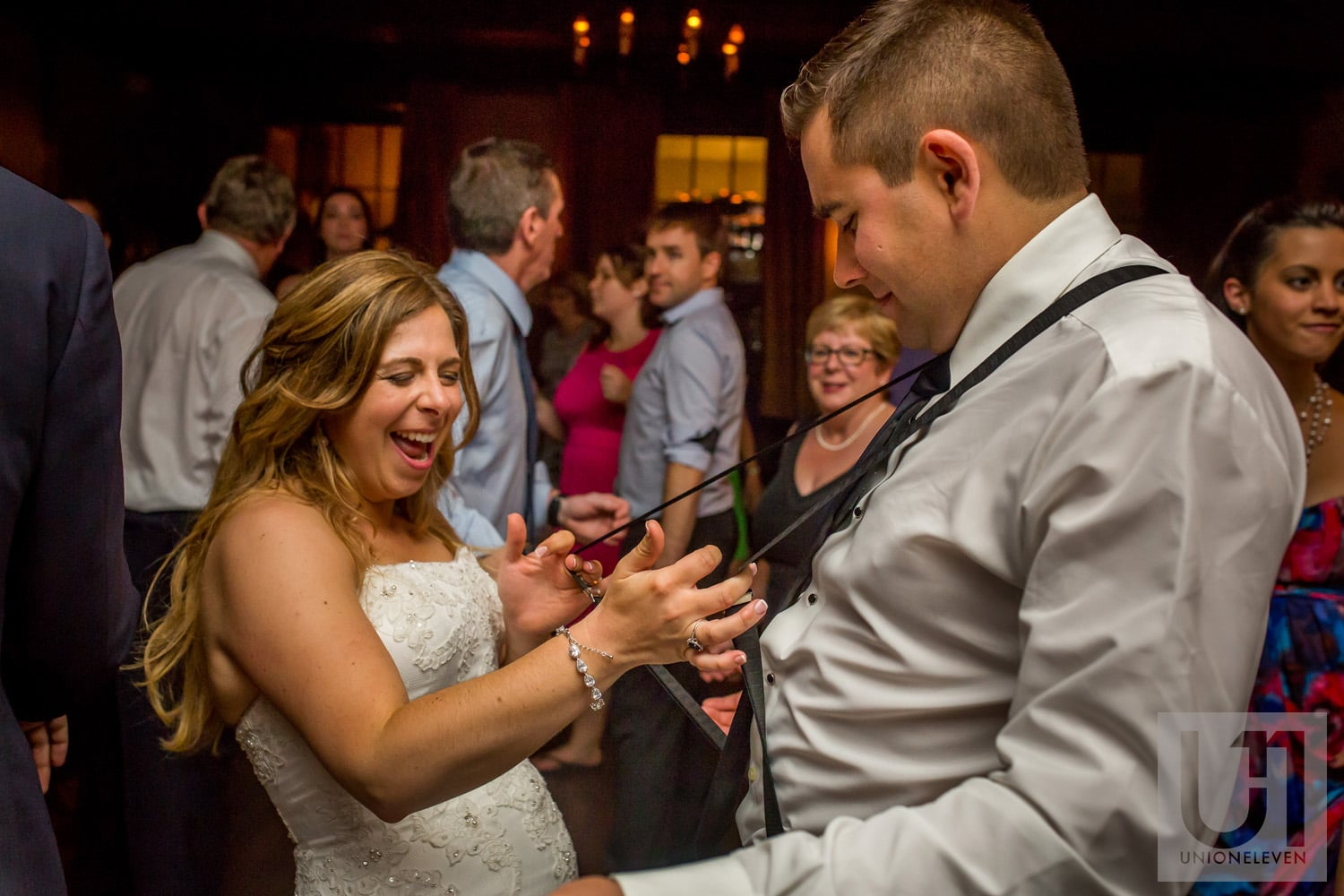 bride dancing with groomsman and pulling on his suspenders at wedding reception